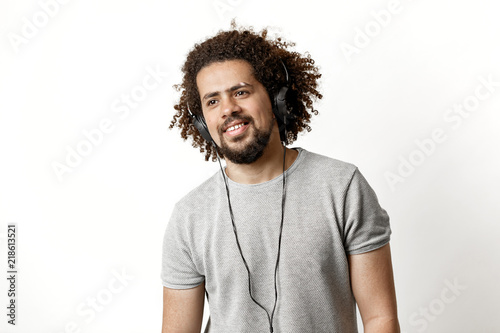 Fotografija A curly-headed handsome man wearing a gray T-shirt and ripped jeans is standing and listening to music in the headphones with a soft smile over the white background