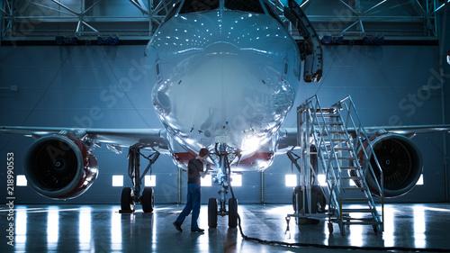 Fotografia Brand New Airplane Standing in a Aircraft Maintenance Hangar while Aircraft Maintenance Engineer/ Technician/ Mechanic goes inside Cabin via Ladder/ Ramp