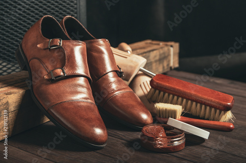 Leather shoes and shoe polish equipment on a wooden composition