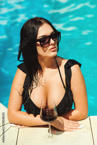 Hot girl with fit body and big boobs Beautiful Brunette Seductive Sexy Rich Luxury Young Woman With Perfect Slim Fit Body In Black Bikini Standing In Swimming Pool Fashion Posing Bright Summer Hot Sunlight Outdoors Big Boobs Copy Space Stock Photo