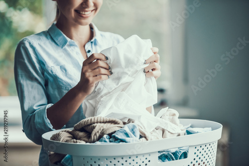 Obraz na plátně Young Beautiful Smiling Woman holds Clean Clothes