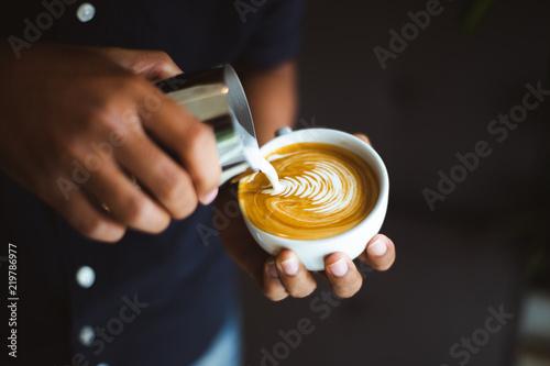 Barista making a cup of coffee latte art in coffee shop.. Fototapete