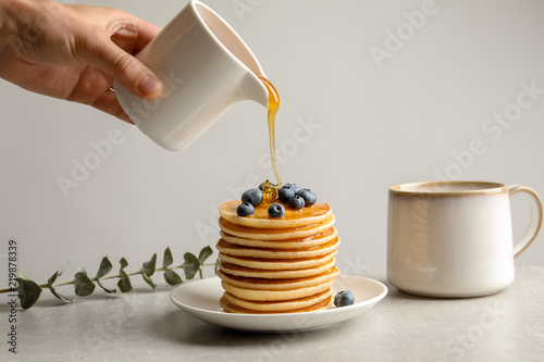 Woman pouring honey onto tasty pancakes with berries on table, closeup