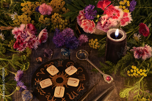 Still life with old runes, zodiac circle, black candle, flowers and ritual objects. Mystic background with ritual esoteric objects, occult, fortune telling and halloween concept