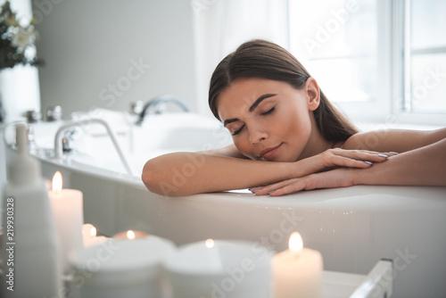 Slika na platnu Portrait of serene female leaning on side of bath while resting there