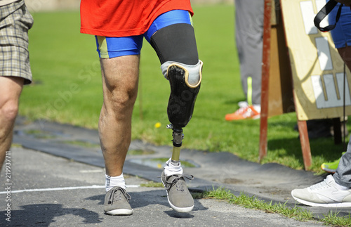 Foto Disabled athlete with an artificial leg walking on a stadium