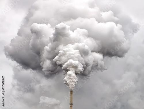 Leinwand Poster Smoke from factory pipe against dark overcast sky