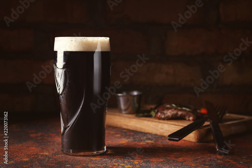 Canvas Print Glass of cold dark beer on color table