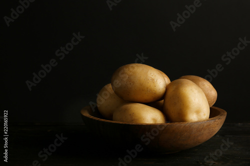 Fresh organic potatoes in bowl and space for text on black background