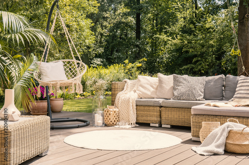 Stampa su Tela A big terrace with a comfortable leisure sofa with cushions, a table and a string swing in a green garden during sunny vacation