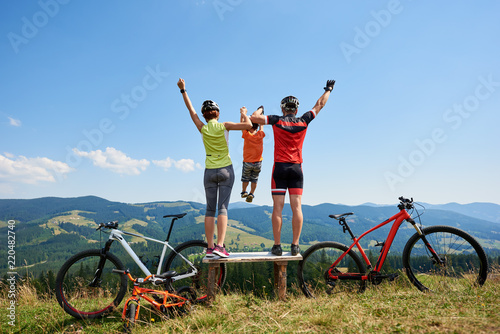 Rear view of family bikers, mom, dad standing on wooden bench with raised hands, holding child in the air, resting after cycling bicycles in mountains. Active lifestyle and happy relations concept.