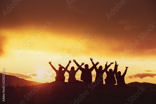 Happy friends with raised arms sunset silhouettes