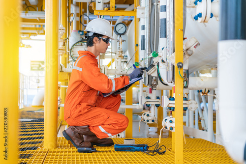 Electrical and instrument operator calibrate level transmitter at offshore oil and gas wellhead remote platform, Onsite service worker Fototapet