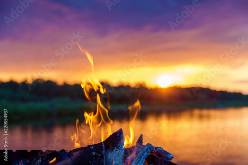Canvas Print bonfire by the river at sunset