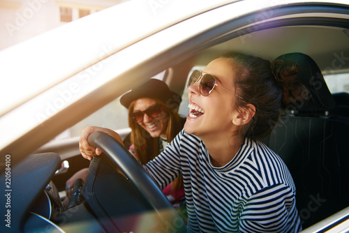 Photo Carefree young friends driving together in a car laughing