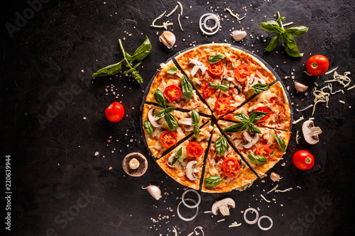 Obraz na plátně Tasty pizza with cherries, onions and mushrooms on a black background