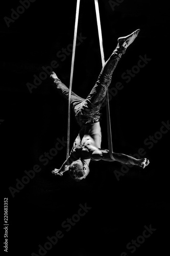 Fototapeta Circus artist on the aerial straps making cross with strong muscles on black bac