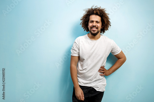 Smiling curly-headed man in white T-shirt with a hand on the hip Fototapeta