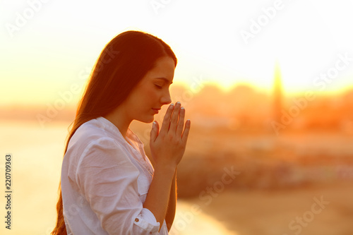 Fototapeta Profile of a concentrated woman praying at sunset