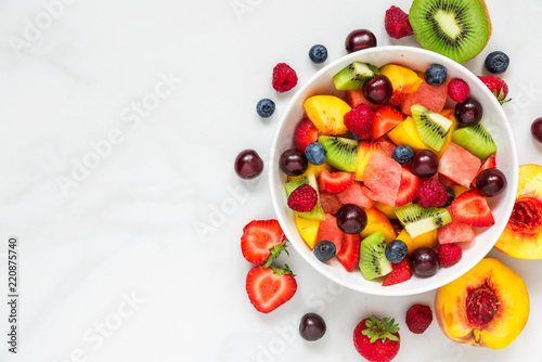 Bowl of healthy fresh fruit salad on white marble background. healthy food. top view