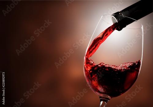 Obraz na plátne Red wine pouring in glass on  background