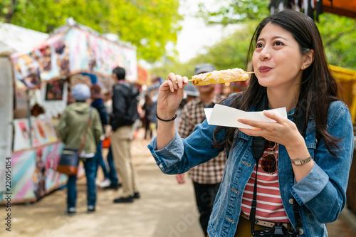 Fotografia gilr eating street food and looking enjoyable