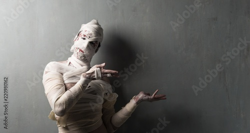Photographie Terrorific mummy pointing to the lateral on textured wall background