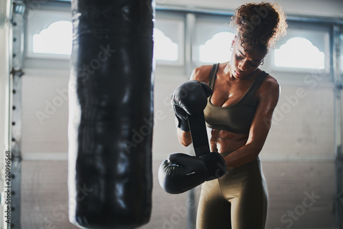 Canvas Print african american woman covered in sweat from boxing punching bag taking off glov