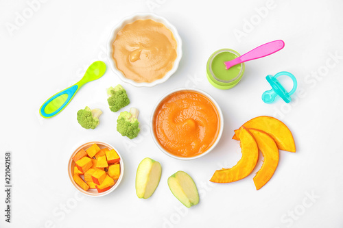 Flat lay composition with bowls of healthy baby food on white background