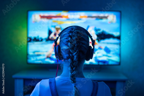 Obraz na płótnie A girl is a gamer or a streamer in front of a television playing