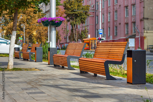 Fotografia The beautiful sunny cityscape with four benches on the sidewalk