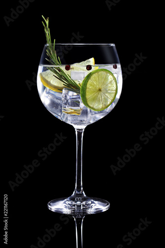 gin tonic garnished with citrus fruit and rosemary isolated on black background