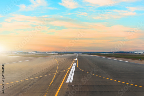 Airport runway after sunset horizon and picturesque cirrus clouds in the sky.