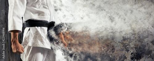 Guy poses in white kimono with black belt. Judo banner