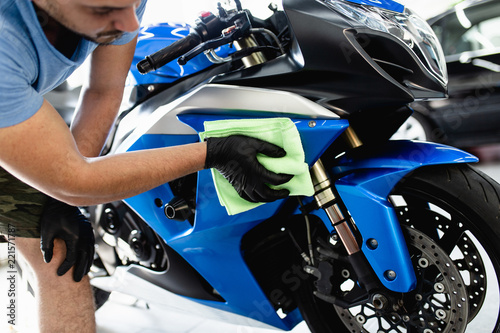 A man cleaning motorcycle with cloth. Selective focus.