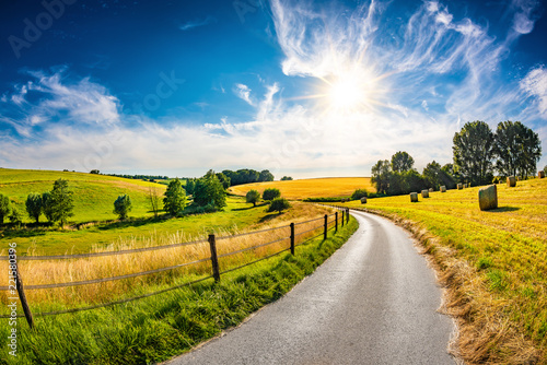 Fotomural Landscape in summer with bright sun, meadows and golden cornfield in the backgro
