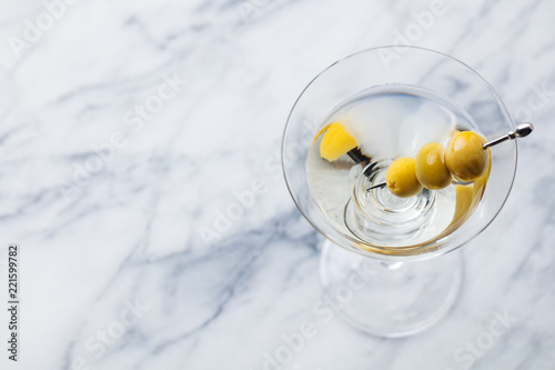Martini cocktail with green olives on marble board. Copy space. Top view.