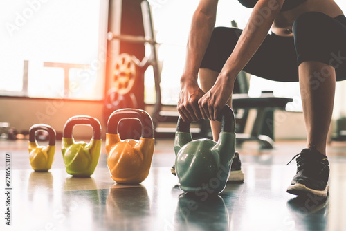 Fotografie, Obraz Close up of woman lifting kettlebell like dumbbells in fitness sport club gym training center with sport equipment near window background