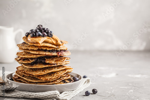 Stack vegan blueberry pancakes with peanut butter and syrup.