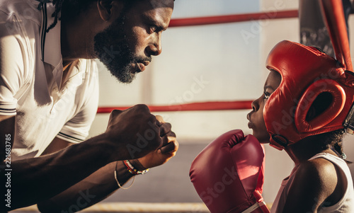 Canvas Print Boxing trainer teaching a kid about boxing