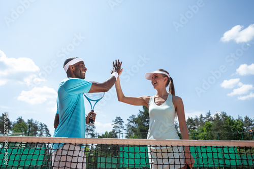 Low angle of happy man and woman standing near net during match in open air. They are giving high-five while celebrating good results. Team sport games for health and pleasure concept