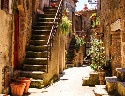 Fototapeta premium Stary dziedziniec w Pitigliano z wazami z kwiatami i ze schodami.