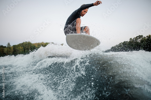 Active wakeboarder jumping on the blue splashing wave against the background of clear sky