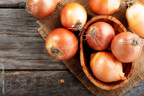 Fotografia Fresh raw onions on wooden background. Top view.