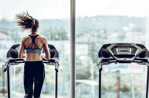 Attractive woman running on treadmill in sport gym Fototapeta