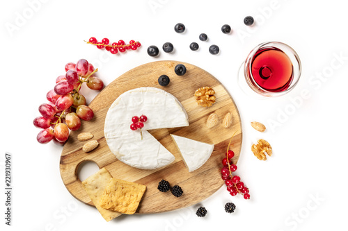 An overhead photo of Camembert cheese with a glass of red wine, fruits and nuts, shot from above on a white background with copy space