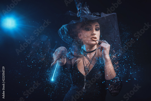 Obraz na płótnie Young witch with a wand and a spellbook casting a spell in her ritual, halloween