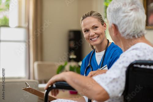 Fototapeta Friendly nurse talking to senior patient