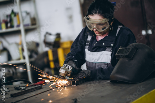 Strong and worthy woman doing hard job in car and motorcycle repair shop. She using grinder to fix some metal bike parts.