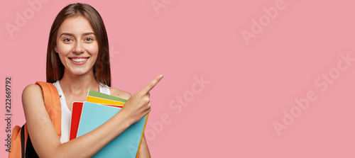 Foto Studio shot of positive Caucasian woman with shining smile, dark straight hair,